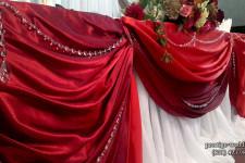 Ткань красного цвете на столе молодых